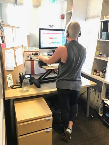 PHOTO: WRITER AMANDA FLETCHER STANDING AT WORK. read her piece about  surviving cancer and shaving her head AS AN ACT OF SELF-LOVE !