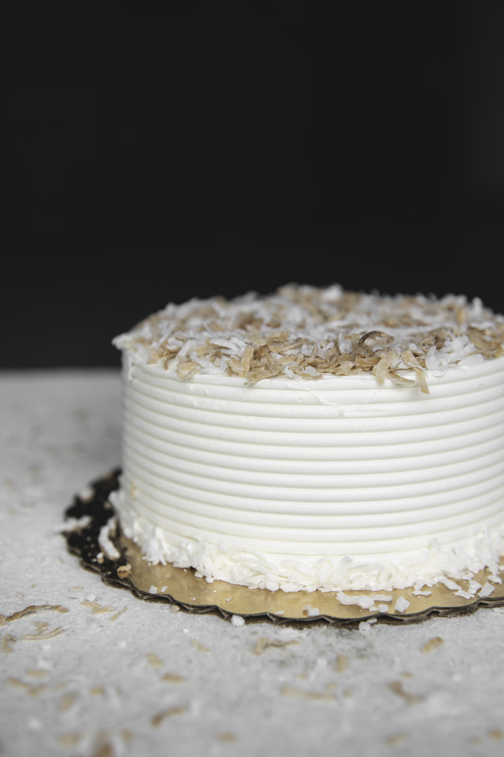 Coconut Cake - This creamy coconut cake is made with coconut puree and piped with a generous serving of coconut buttercream. Tiki torches recommended but not required.