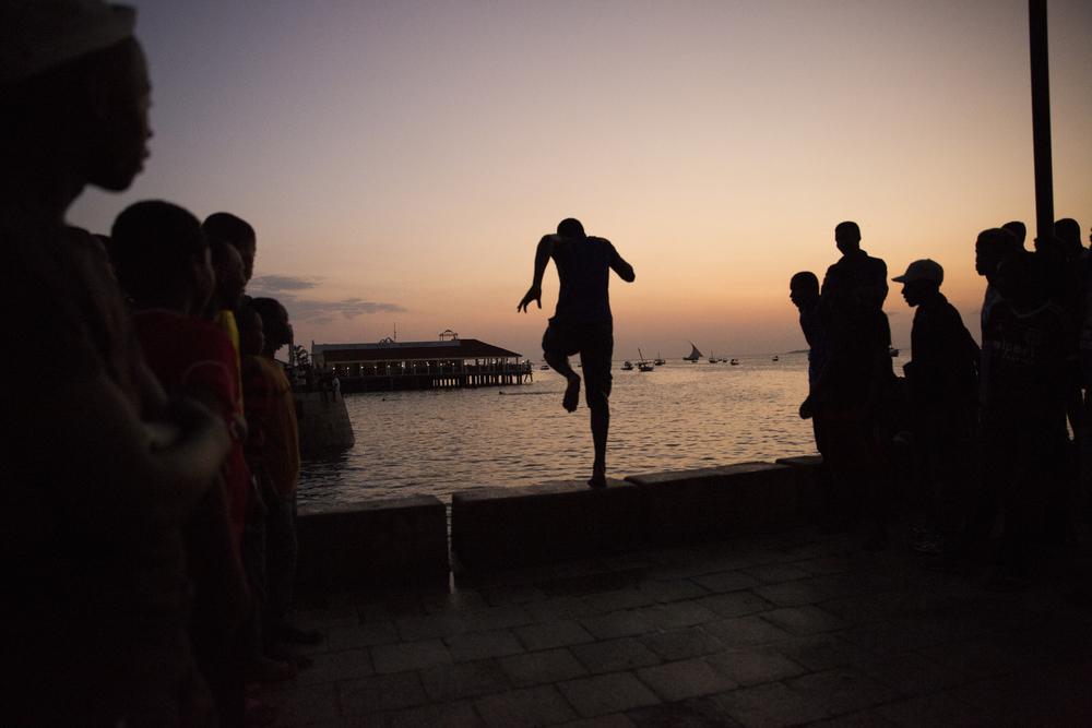 Zanzibari boys take turns diving into the bay in Stone Town, Zanzibar.