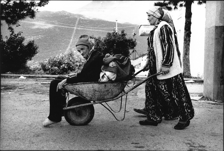 A Kosovar refugee is transported across the border from Kosovo to Albania by his wife.