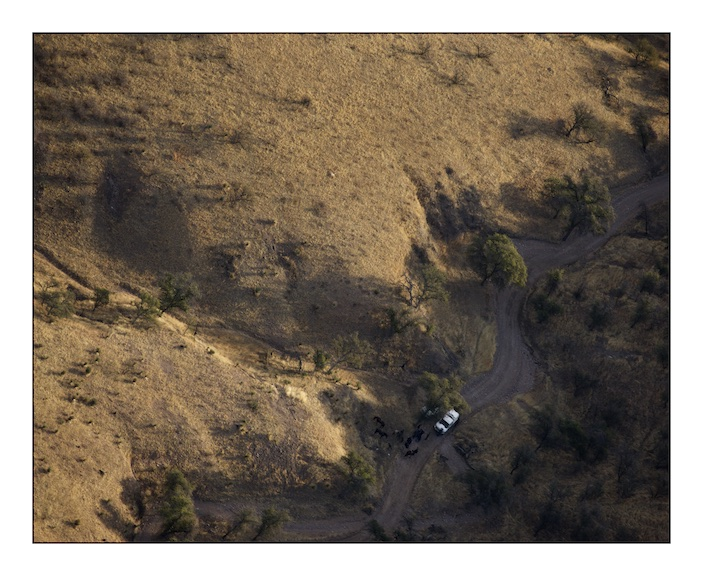 Two United States Border Patrol vehicles parked next to their horses on a trail in Baboquivari Mountains in the Sonoran desert. The Border patrol use horses to patrol remote areas where their vehicles cannot pass.