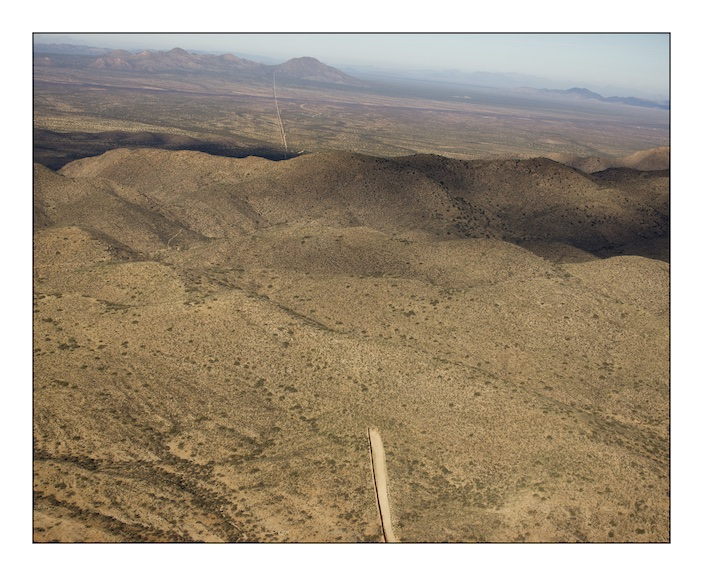 The border fence between Mexico (on the left) and the United States (on the right) stops abruptly as the Baboquivari Mountains rise out of the desert near the hard scrabble town of Sassabe that straddles the border in southern Arizona. The fence costs over one million dollars per mile and in areas where the terrain is especially harsh and dangerous to cross the construction halts. The consequence of this is that migrants are forced into areas where human life is incredibly difficult to sustain and they die.