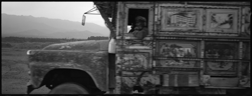 An old truck races north on the Old Road from Kabul to the Panjshir Valley through a heavily landmined area.