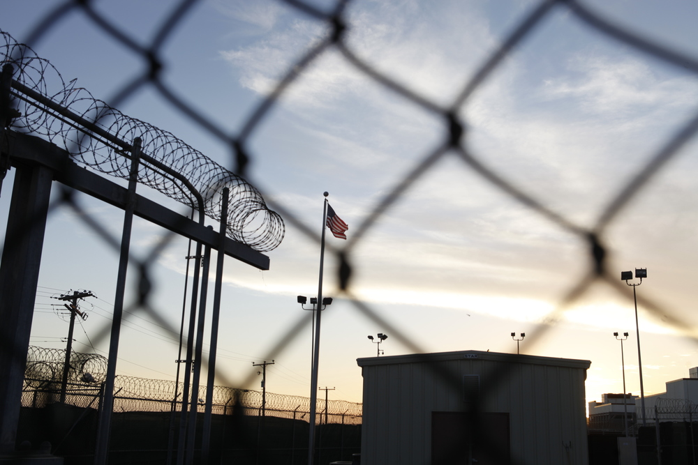 February 2014: The American flag can be seen through a barbed wire fence inside Camp 5 as the sun sets on Guantanamo Bay. Copyright: ICRC/Anna Nelson