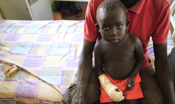 A child with a gunshot wound to his hand rests on his father's lap as he undergoes medical treatment at the general military hospital in Juba, 28 December 2013. © Reuters/James Akena