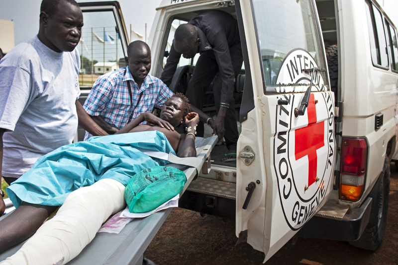 South Sudan: ICRC staff carry a patient on a stretcher to the plane that will transport him to hospital, where he will undergo surgery. © ICRC / C. Lepage / ss-e-00209