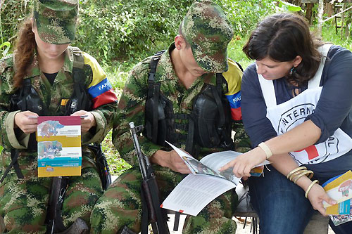 Guaviare state, San José del Guaviare. An ICRC delegate speaks with members of FARC-EP (Revolutionary Armed Forces of Colombia) while they peruse ICRC brochures, during a dissemination session on international humanitarian law (IHL). © ICRC / B. Mosquera / co-e-01956