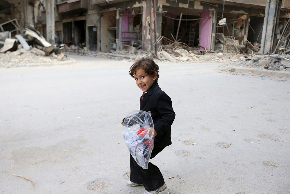 "Our photo of the week was taken from an Atlantic photo gallery titled ""Syria's Children."" In this photo a boy carries a bag of new clothes ahead of the Eid al-Fitr holiday marking the end of Ramadan in Jobar, a suburb of Damascus, Syria, on July 15, 2015. © Bassam Khabieh / Reuters"