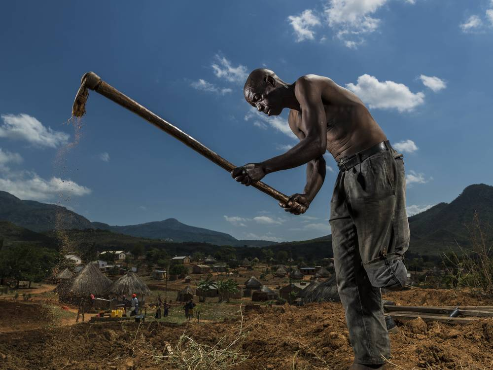 BARRIO CHIUIJO, MOZAMBIQUE: Bonafacio Muazia, 57, lost his left leg to an anti-personnel landmine in 1985 during the civil war. However, he continues to farm, having developed extraordinary balance. With his wife carrying the hoe, every day he hobbles 45 minutes each way to his garden. Brent tirton/Getty Images/ICRC.