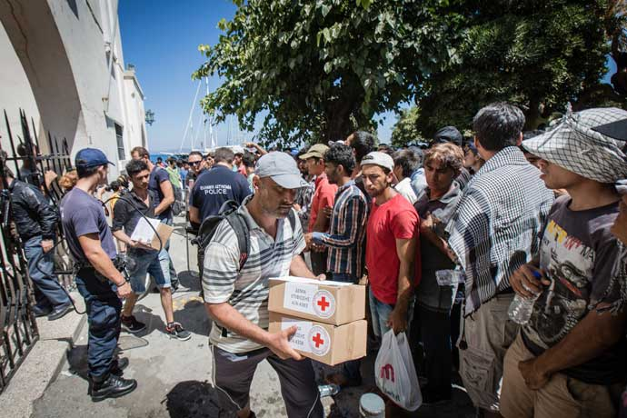 A man leaves the registration centre to rejoin his family, carrying relief items provided by Hellenic Red Cross, as well as his all-important registration papers. Stephen Ryan/IFRC