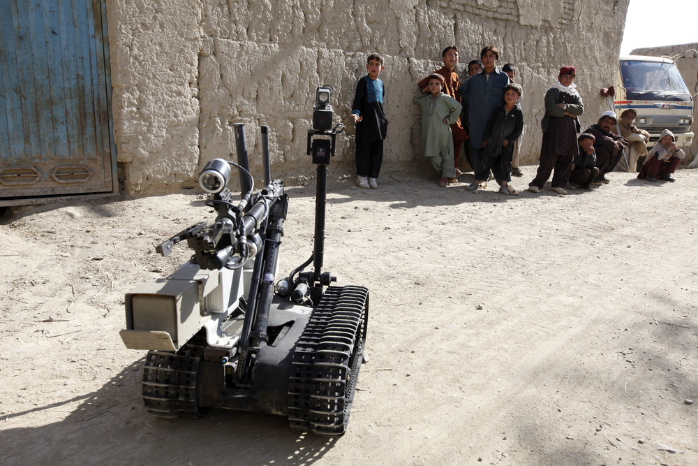 Afghan residents look at a robot during a road clearance patrol in logar providence.  ©umit bektas, reuters.