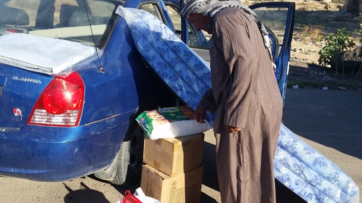 Um Arrizam, Libya, 14 October 2015. A man loads his car with household items. The ICRC distributed essential household supplies to 1,320 internally displaced persons from Derna, Alfatayih and Benghazi who have taken refuge in and around Um Arrizam. CC BY-NC-ND / ICRC / Fares Elabeid