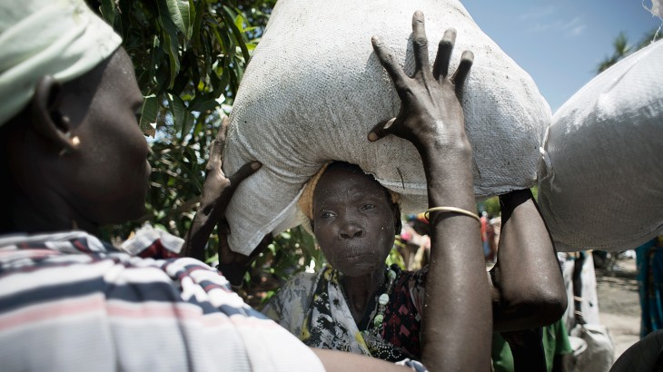 Unity State, Leer, South Sudan. A man helps a woman to heave a bag of sorghum on her head at an ICRC food distribution. ©Jacob Zocherman/ICRC