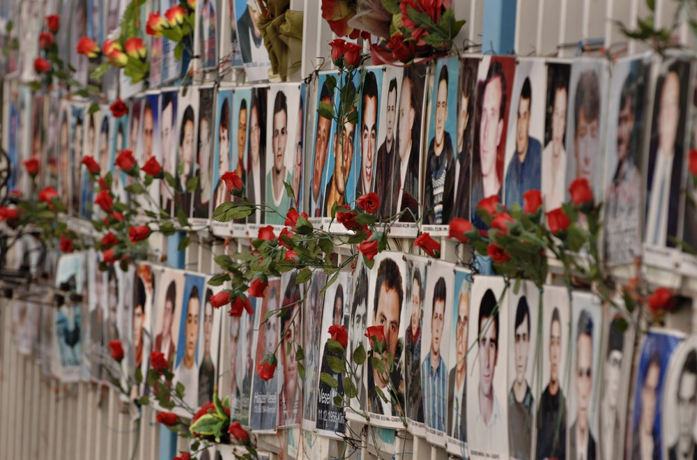 Pristina. Pictures of missing persons hanging on a fence outside a public building. Fresh flowers are attached to many of the portraits of people that have been missing since the war that ended in 1999. ©SALTBONES, OLAV/ICRC