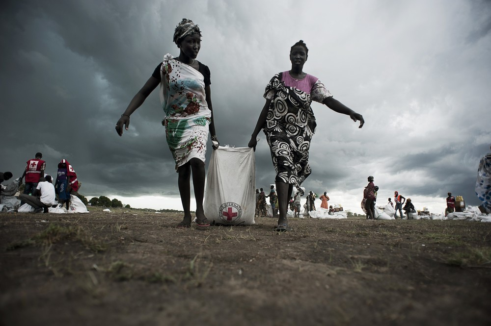 Unity State, Leer. Women collecting sorghum and oil some hours after an airdrop conducted by the ICRC.  ©ZOCHERMAN, JACOB/ICRC