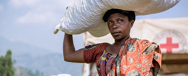 A woman carries a sack of seed that was distributed by the ICRC to displaced persons in South Kivu, Democratic Republic of Congo.  © Alyona Synenko/ICRC