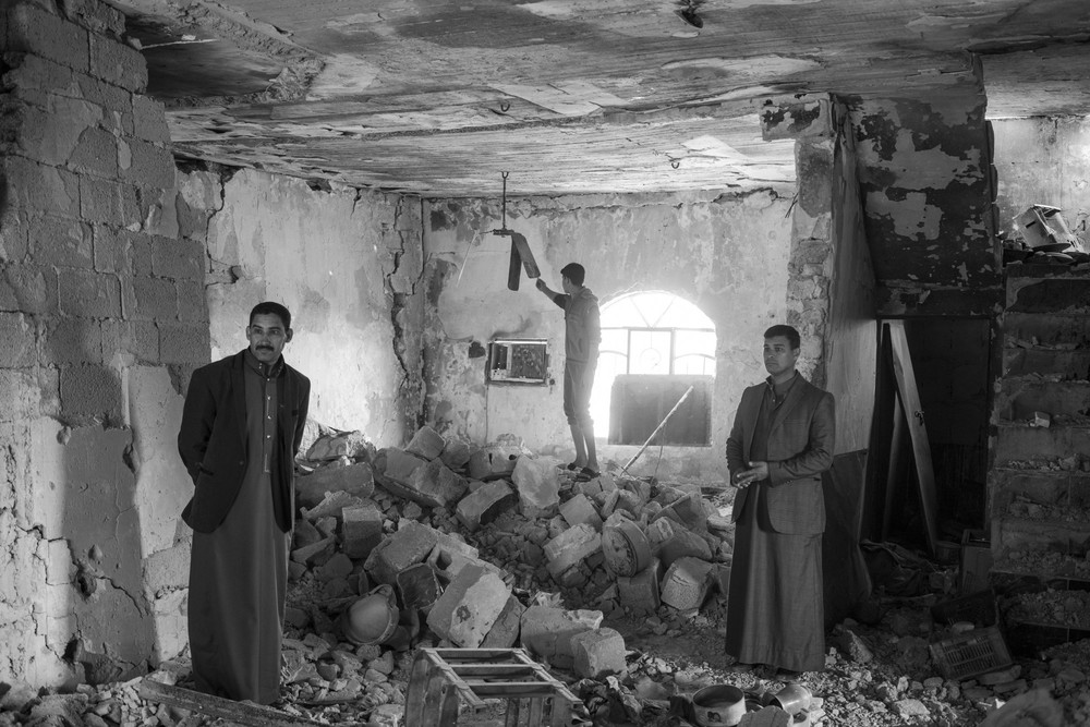 A family surveys the damage to their house in Albu Ajeel, which was bombed by armed groups as they retreated from the area last year. Moises Saman/Magnum Photos for ICRC