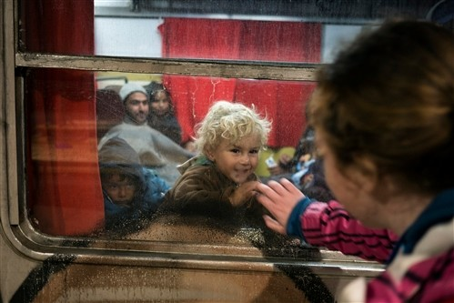 A child waves to a Slovenian Red Cross member just before the train departs for Austria. ©Thomas DWORZAK/ICRC