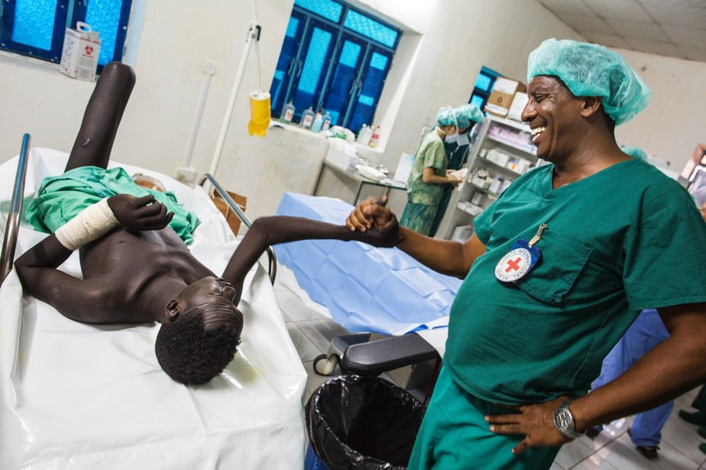 Surgeon Manuel Lopez greets Kay Lieny, a patient that recently underwent an amputation after being shot while herding his cattle.