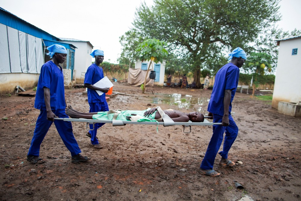 Porters carry a patient from the Intensive Care Unit of the hospital.