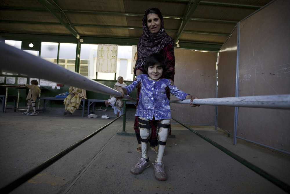Kabul, ICRC orthopaedic centre. A young girl practices walking with her orthoses.