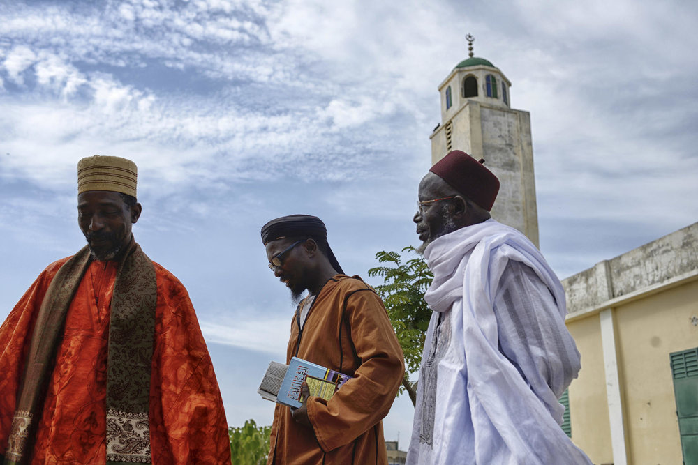Clergy leave a mosque in Guediawaye, a small village in Senegal where two women were recently arrested for alleged ties to extremists. Photo courtesy of Samuel Aranda/The New York Times.