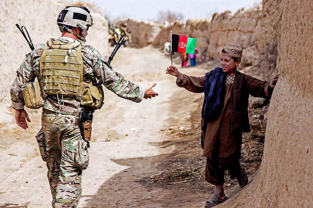 An Afghan child waves a flag at a member of coalition forces as he patrols to a medical clinic led by Afghan national security forces in the Panjwai district of Afghanistan's Kandahar province. (Photo Courtesy: Department of Defense)