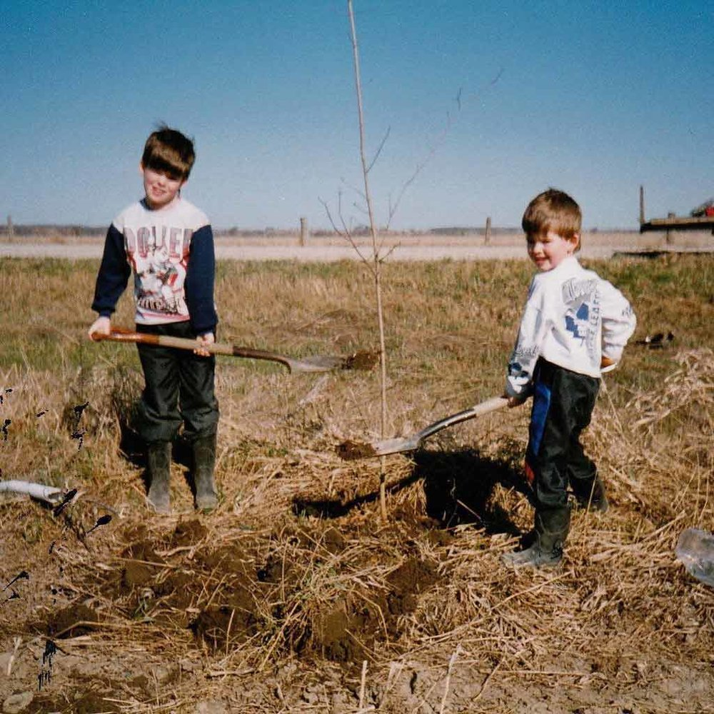 Company owner Ryan (right) and his older brother Jeff (left), planting one of the many trees that line their streets today