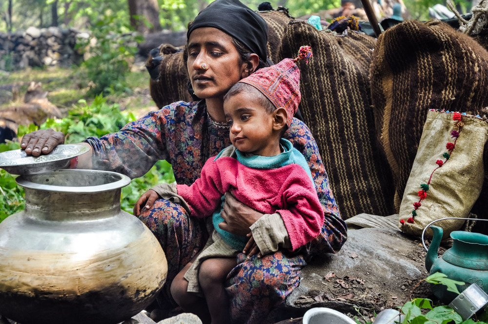 Jamila cooks while holding Yasin, at a camp in the forest