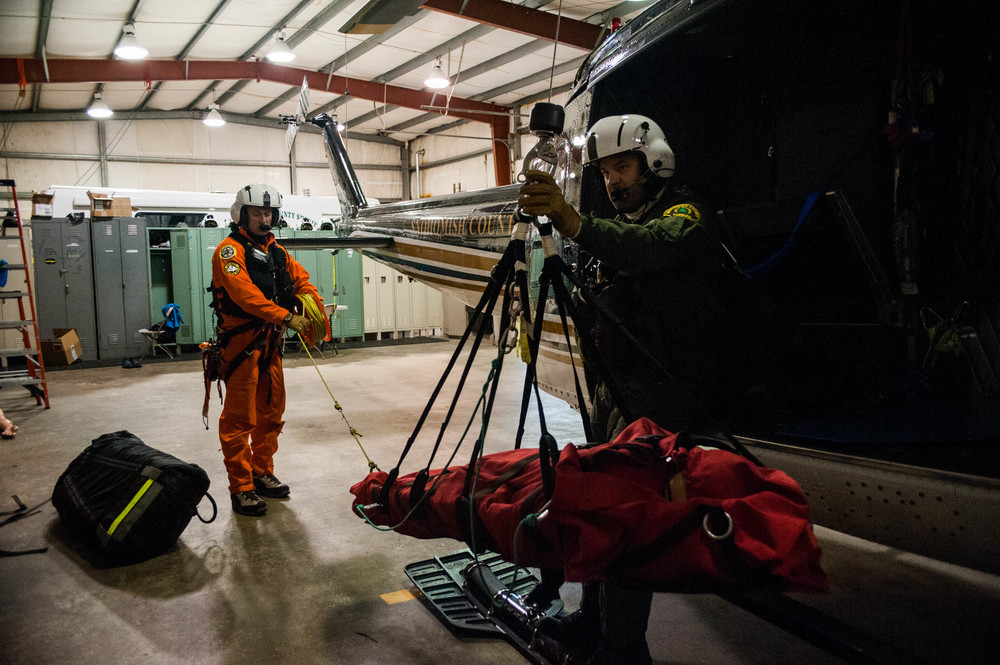 Oyvind Henningsen (left) and deputy Beau Beckner practice hoisting a rescue litter into SnoHawk 10, a helicopter used by the Snohomish county search and rescue helicopter team, during a training exercise. The crew typically performs training drills inside of the hangar before flying out to their training locations to make sure that everyone is following proper procedure.