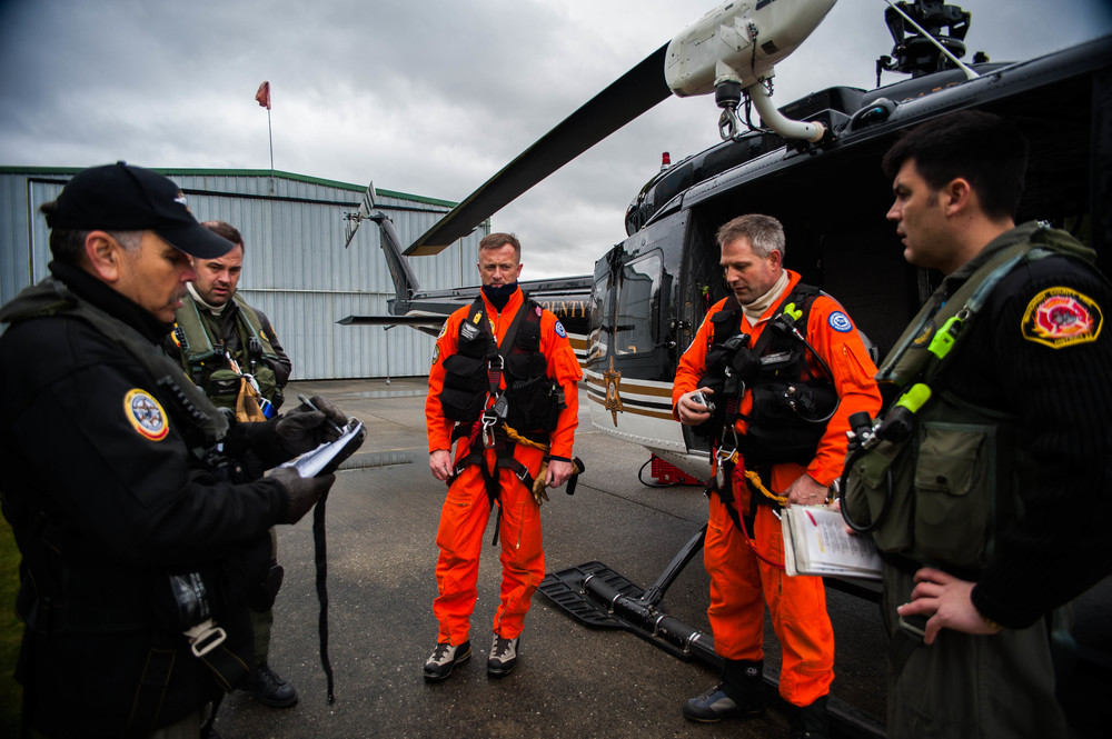 Chief Pilot, Bill Quistorf, briefs the rescue team prior to flying out for a scheduled helicopter rescue training exercise. The crew consists of five members, from left to right, Quistorf, Deputy Beau Beckner, the crew chief, Oyvind Henningsen and Ernie Zeller, who are both rescue technicians and Travis Hots, the co-pilot. The crew will fly to a predetermined location in the mountains to perform rescue drills and it is important that they go over risk factors and safety protocols as a team before they leave.