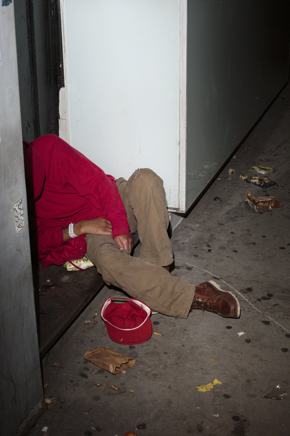 New York, USA - November 06, 2015: A man sleeps in a doorway on the corner of Bowery and Stanton St. The Bowery Mission some blocks away, tries to take care of those living on the street. The Bowery, a street and neighborhood in Manhattan, once home for vagrants and a diversity of subcultures became the playground of artists, fancy bars and real-estate tycoons.