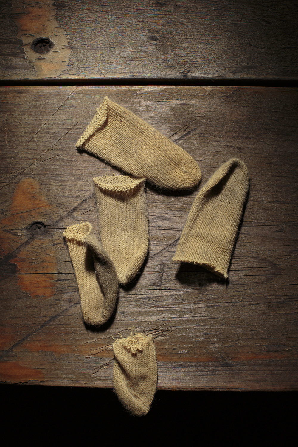 New York, USA - November 06, 2015: Cut off fingertips of cotton gloves lie on a wooden table on Chrystie St. The Bowery, a street and neighborhood in Manhattan, once home for vagrants and a diversity of subcultures became the playground of artists, fancy bars and real-estate tycoons. 