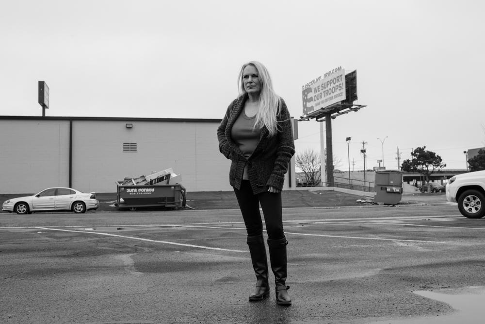 """05 Jan 2016 - Amarillo, Texas - Verfechterin der republikanischen Ideale Susan Allen posiert auf einem Parkplatz und blickt in Richtung Hauptsitz der Partei an der 4217 SW 21st Ave.  Im Hintergrund ist eine Tafel mit den Worten """"WE SUPPORT OUR TROOPS!"""" zu sehen. Amarillo ist eine der konservativsten und republikanisten Städte der USA und stimmte mit einer überragenden Mehrheit gegen Obama in den Präsidentschaftswahlen 2012. Photo Credit: Cédric von Niederhäusern"""