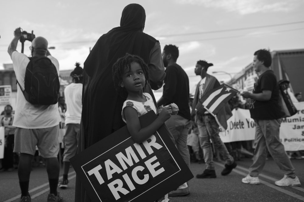 "26 July 2016 - Philadelphia, PA - A girl is holding a sign at the ""Shut Down the DNC!"" march to remember the shooting of 12yr old Tamir RIce in Cleveland, OH. 