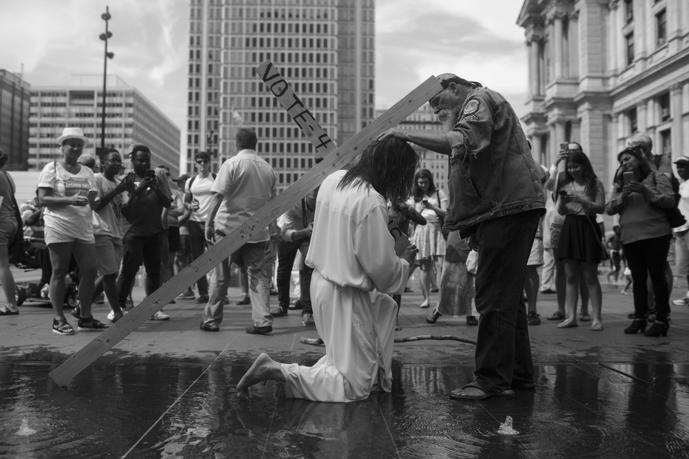 26 July 2016 - Philadelphia, PA - A man dressed up as Jesus interacts with Gary Mathes (r), who is carying around a cross during the Democratic National Convention.