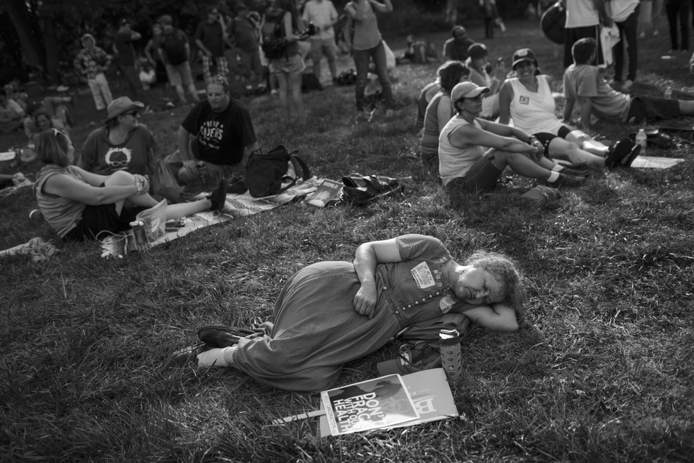 24 July 2016 - Philadelphia, Pennsylvania - A women is laying in the grass at FDR after a long and hot march. A day prior to the Democratic National Convention  Bernie supporters gather for a rally from City Hall to Franklin Delano Roosevelt Park.