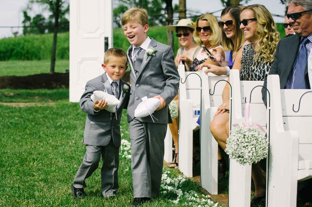 Ring bearers walking down aisle at wedding ceremony