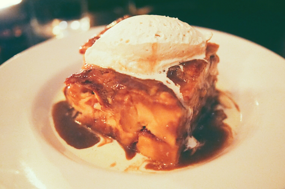 brioche bread puddingwith creme anglaise, cinnamon caramel and whipped cream.