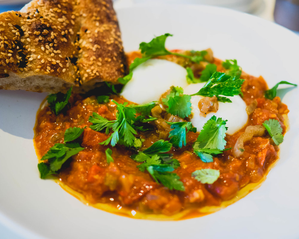 shakshuka: poached eggs in tomato stew, bread.