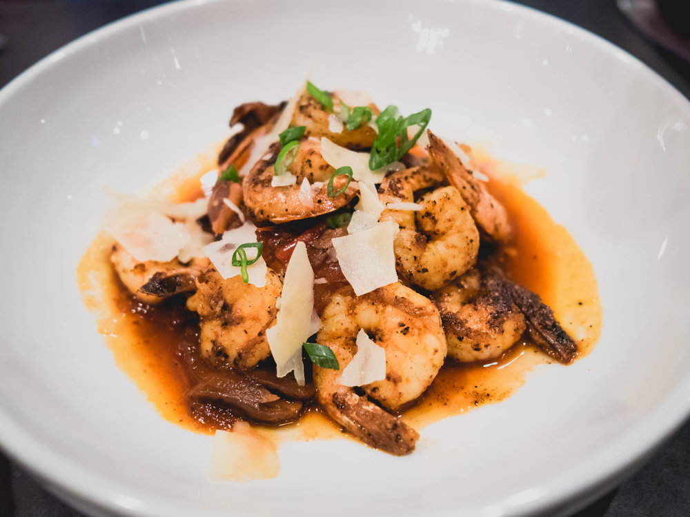 shimp & grits : cajun seared gulf shrimp, mushrooms, onions, peppers, smoky lager sauce, cheese grits.