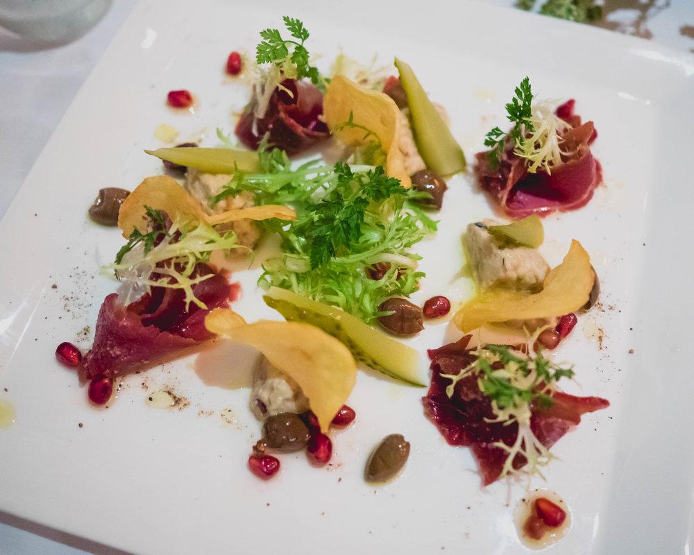 lebanese basturma at senses: thin sliced dried lebanese beef, babaganoush, pomegranate, herbs.
