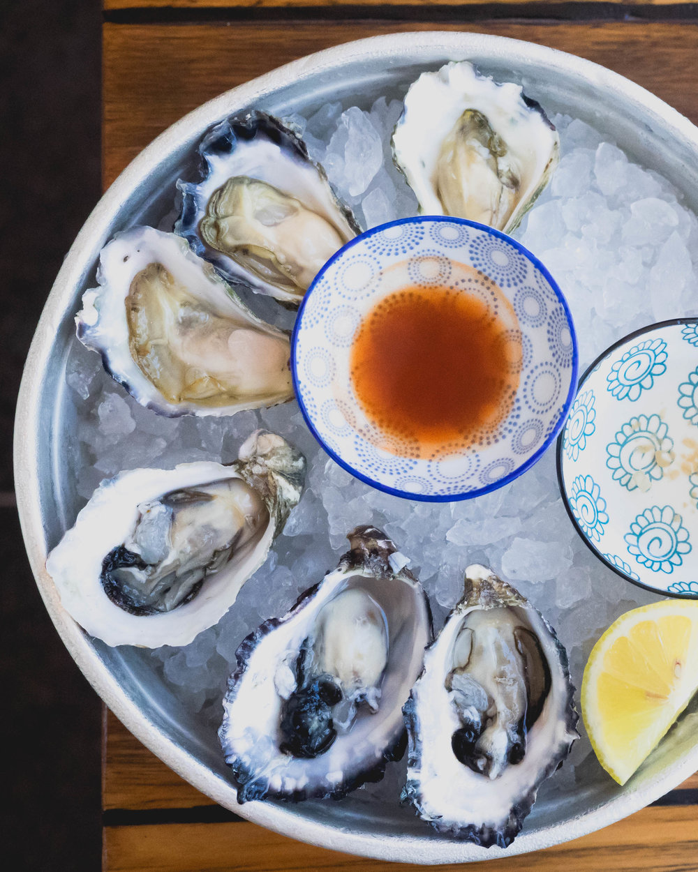 pacific and sydney rock oysters with hot sauce, lemon, mignonette .