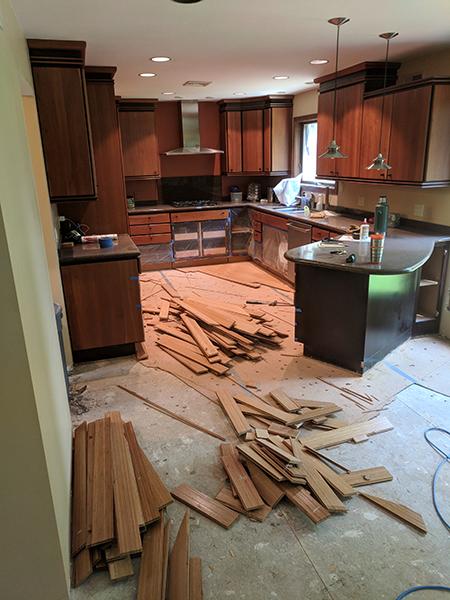 Demoing original kitchen wood floor in preparation for the Warm Board installation.