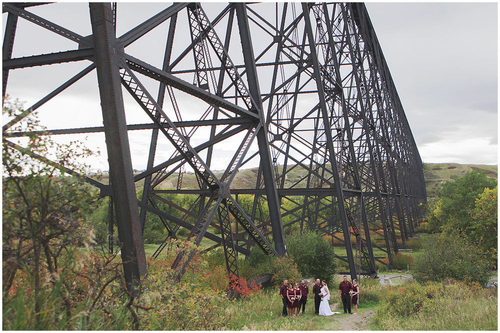 Lethbridge High Level Bridge wedding party   A stunning Fall wedding in Lethbridge Alberta - a religious church ceremony at the URC Church with stained glass windows, a quick stop at the Wooden Shoe for lunch and bridal party pictures at Indian battle park.  #albertawedding #lethbridge #redwinewedding #redcolourscheme #babiesbreathboquet #indianbattlepark #woodshoe #overcastwedding #fallwedding #kissingcouple #brideandgroom #emotionalwedding #church #churchceremony