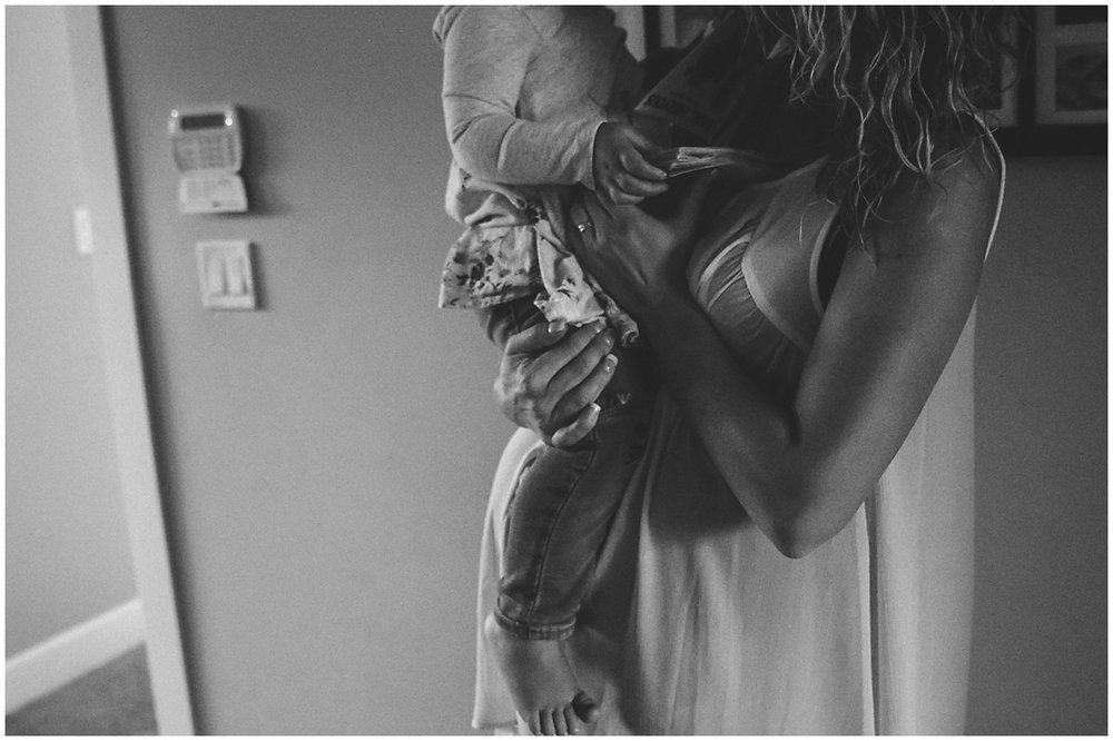 pregnant mother holding child on belly  #documentaryphotography #lifestlyephotography #vancouver #langley #fraservalley #mother #father #kids #trampoline #jenga #booknook #lifestyle #inhome #fall #familyof5 #fourthbaby #maternity #reading #whitekitchen #activefathers #playwithyourkids