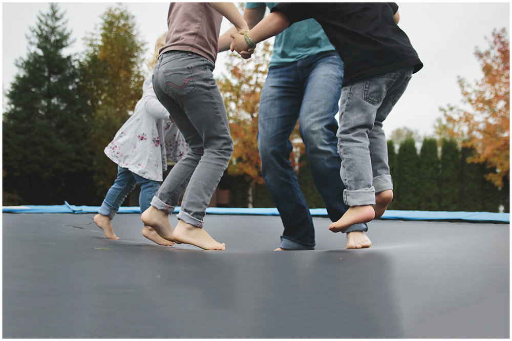 family of feet jumping on a trampoline in a fall backyard  #documentaryphotography #lifestlyephotography #vancouver #langley #fraservalley #mother #father #kids #trampoline #jenga #booknook #lifestyle #inhome #fall #familyof5 #fourthbaby #maternity #reading #whitekitchen #activefathers #playwithyourkids