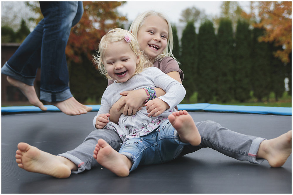 two sisters laughing while being bounced on the trampoline  #documentaryphotography #lifestlyephotography #vancouver #langley #fraservalley #mother #father #kids #trampoline #jenga #booknook #lifestyle #inhome #fall #familyof5 #fourthbaby #maternity #reading #whitekitchen #activefathers #playwithyourkids