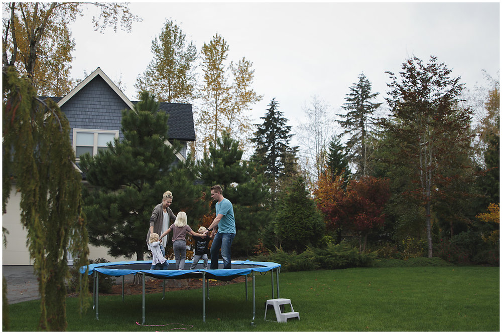 family jumping on the trampoline in fall backyard  #documentaryphotography #lifestlyephotography #vancouver #langley #fraservalley #mother #father #kids #trampoline #jenga #booknook #lifestyle #inhome #fall #familyof5 #fourthbaby #maternity #reading #whitekitchen #activefathers #playwithyourkids