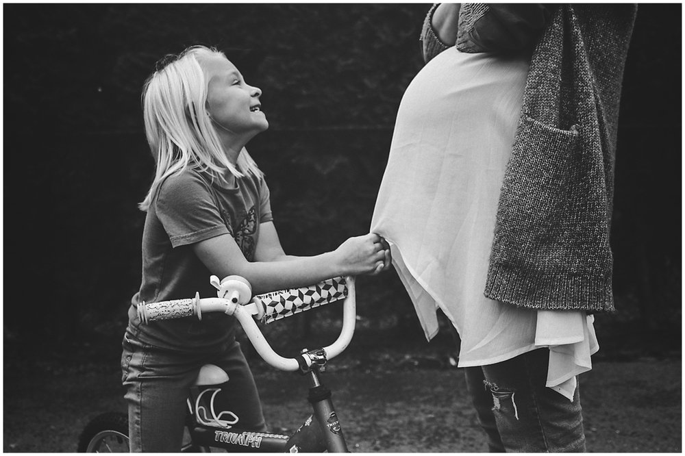 daughter tugging on pregnant mother's shirt  #documentaryphotography #lifestlyephotography #vancouver #langley #fraservalley #mother #father #kids #trampoline #jenga #booknook #lifestyle #inhome #fall #familyof5 #fourthbaby #maternity #reading #whitekitchen #activefathers #playwithyourkids